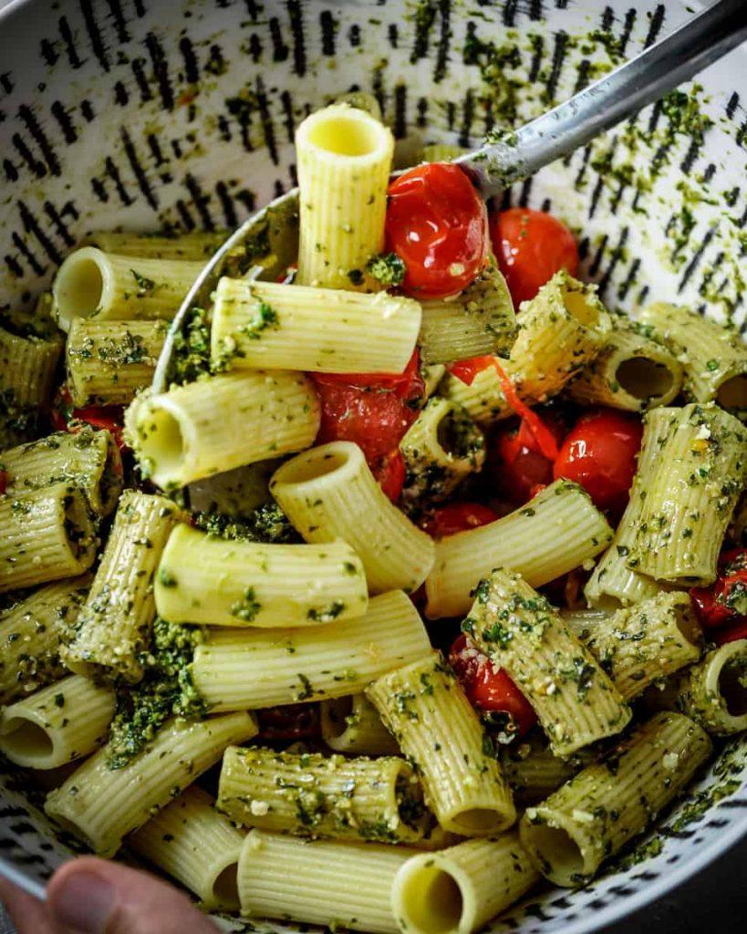 stirring together vegan rigatoni and pesto