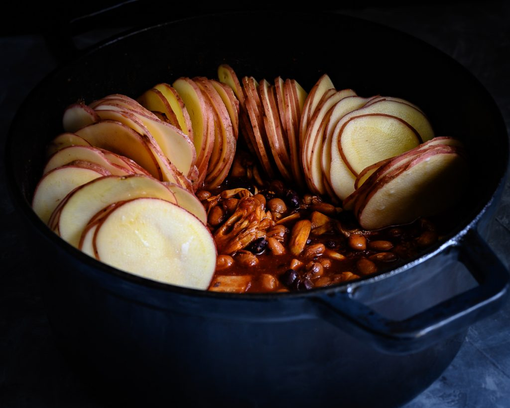 topping the chilli with sliced potatoes